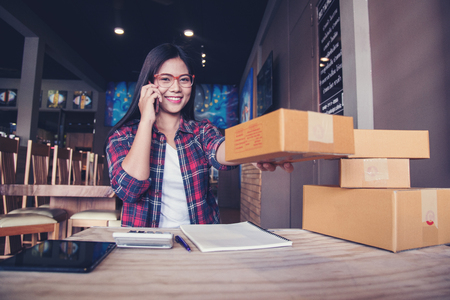 Young entrepreneur, teenager business owner work at home, box for delivery Banco de Imagens