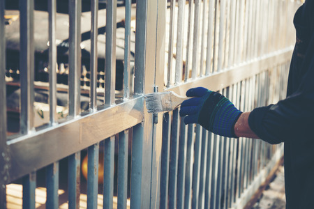 Construction worker painting fence at home, closeup