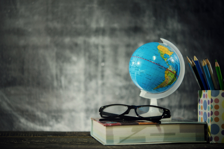 Education or back to school Concept.world globe,books, glasses, pencils, over chalkboard background.