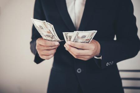 finances, economy and business concept. close up of Businessman with money on hand Banco de Imagens