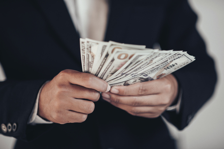finances, economy and business concept. close up of Businessman with money on hand Imagens