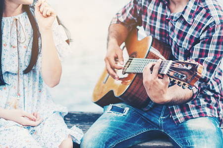 Couple in love with playing guitar at river