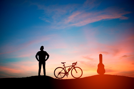 Lifestyle hipster man standing on the mountain with bicycle and acoustic guitar. sunset background