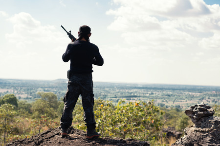 Soldier on the top of a mountain with hand holding gun