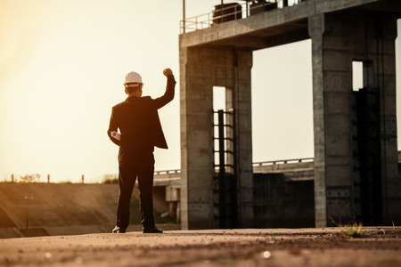 Business Industrial,People,personal and career growth, progress and potential concepts.Businessman engineer looking blueprint in a dam site.silhouette engineering working in site