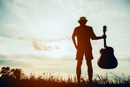 Musician holding acoustic guitar and walking in summer fields with sunset Stockfoto