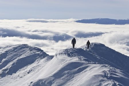 two climbers on a mountain top in winter, Piatra Craiului Mountains, Romania Stock Photo
