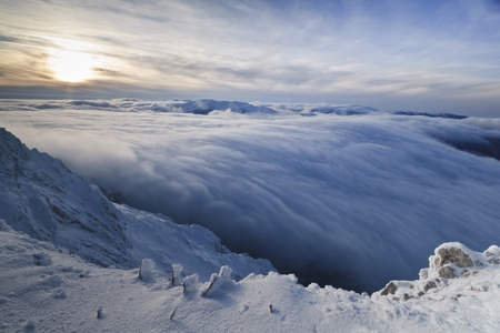 a beautiful sunset over the mountains and clouds in winter Stock Photo