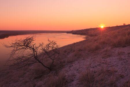 sunrise on the shore of a lake photo
