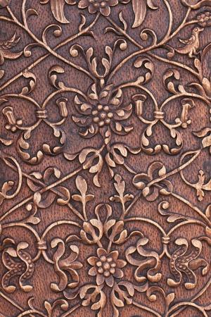 una scultura tradizionale su una vecchia porta di legno