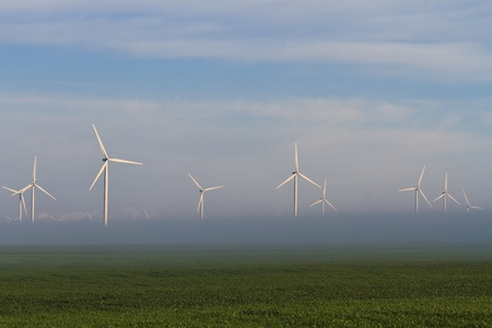 wind power turbines on a hill in fog