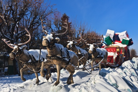 a carriage pulled by four reindeer with gifts