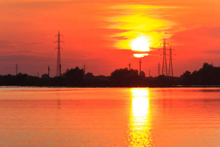 sunset landscape with high voltage electricity power line. photo