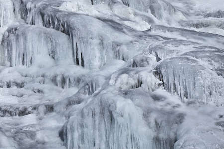 a beautiful waterfall on a mountain river in winter photo