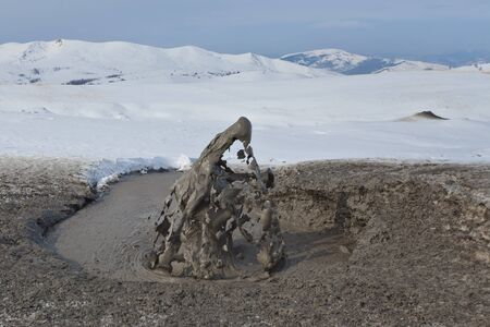 mud and snow: a mud volcano crater in winter. Buzau, Romania Stock Photo