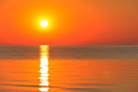 reflection of the sun at sunrise at sea photo
