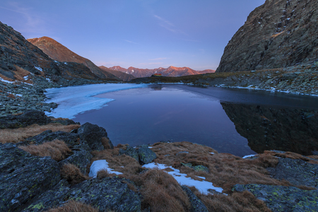 fagaras: sunset in Caltun lake. Fagaras Mountains, Romania Stock Photo