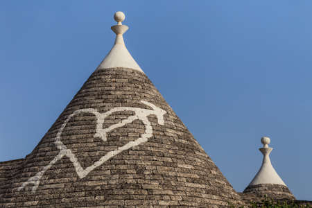 trulli: Trulli houses with painted symbols on the conical roofs in Alberobello, Italy