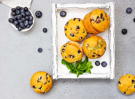 Blueberry muffins with thyme, mint and fresh berries in a light wooden tray. Gray concrete background. Top view.