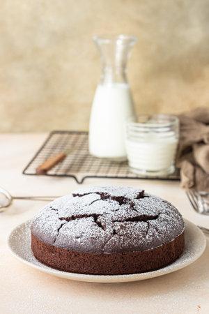 Chocolate sponge flourless cake with sugar powder, light concrete background. Brownie cake. Toned image. Selective focus