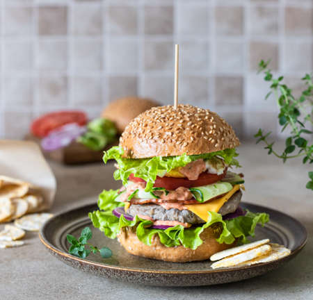 Tasty fresh homemade beef burger on ceramic plate with ingredients for making on background. Fast food and junk food concept. Selective focus.