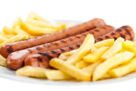 tres wurstel delicioso en un plato blanco con papas fritas francés Foto de archivo