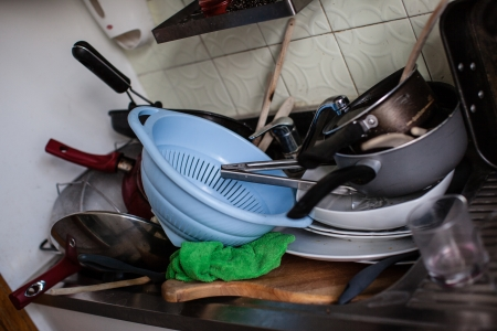 un montón de ollas sucias, vasos y otros utensilios de cocina en un fregadero