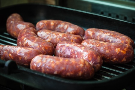 Cooking a succulent and spiced sausage on a grilling pan photo