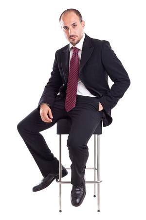 an elegant businessman sitting on a footstool