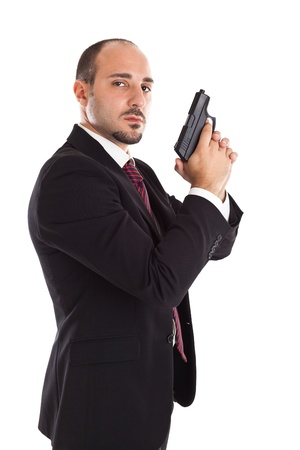 a well dressed businessman with a gun posing like a secret agent