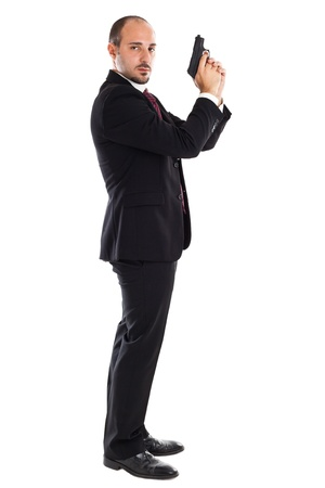 james: a well dressed businessman with a gun posing like a secret agent