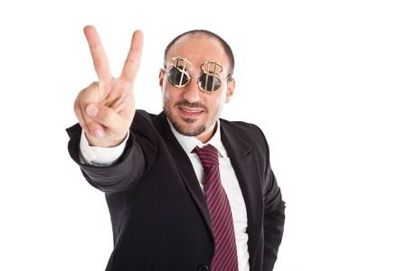 Businessman with dollar-sign glasses standing and showing the win sign photo