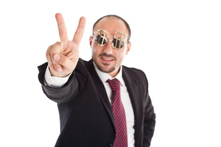Businessman with dollar-sign glasses standing and showing the win sign. Focus on the hand photo