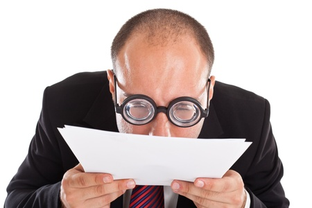 A businessman wearing thick, circle glasses tryng to read some documents