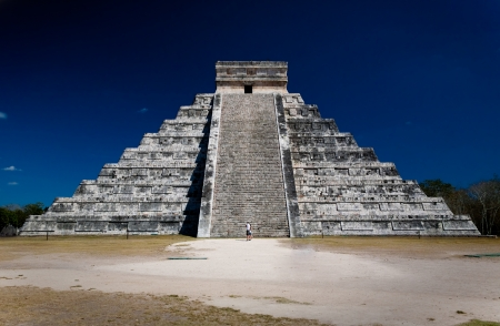 Zigurat (pirámide) en Chichén Itzá con dos personas mirando en frente de la escalera. Cielo azul oscuro