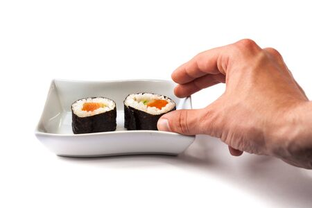 Tasty maki sushi holded by a male hand over a white background photo
