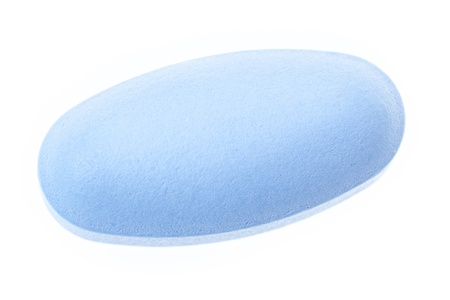 Extreme macro of a single pill over white background