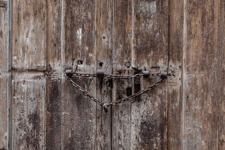 an old and ruined red door with a padlock and chain photo