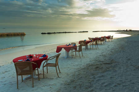 Five tables and some chairs on a tropical beach at dusk photo