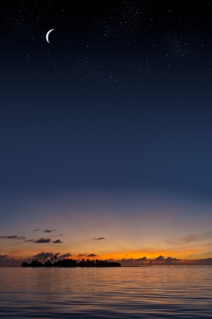 Tropical sunset with an island shilouette under a starry sky