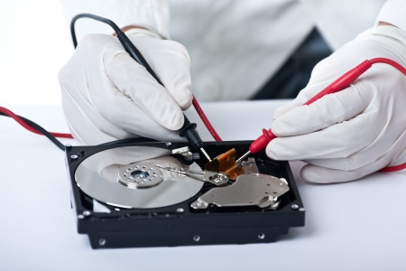 conductor electricity: A technician repairing an hard disk with a tester
