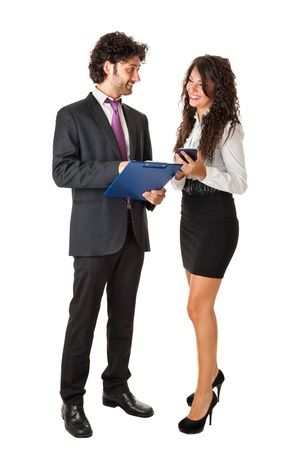 An elegant businessman and a beautiful businesswoman with a clipboard and an office calculator doing some paperwork