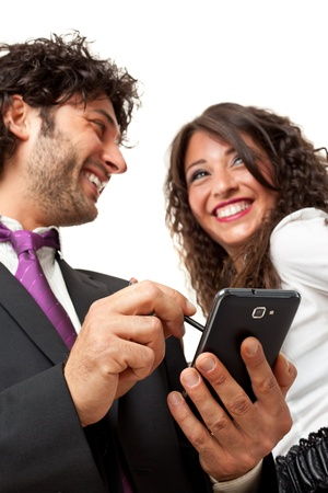 Bright shot of a gourgeous business couple using a smartphone over a white background photo