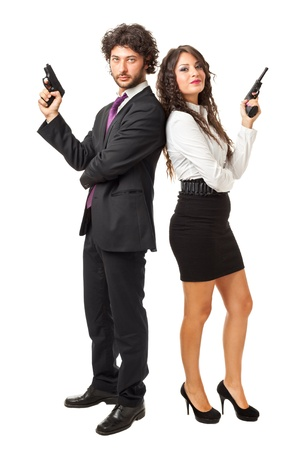 A businessman and a businesswoman (or maybe a couple of spies or gangster) holding guns over a white background Stockfoto