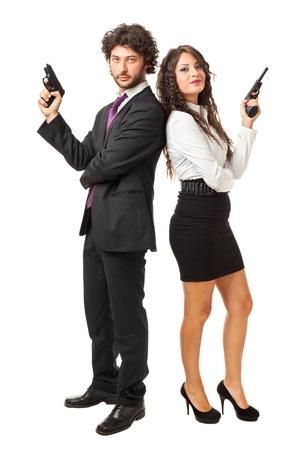 pistolas: Un hombre de negocios y una mujer de negocios (o tal vez un par de esp?as o mafiosos) celebraci?n de las armas en un fondo blanco