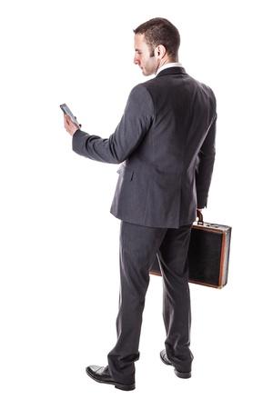 un hombre de negocios bien vestido, de pie sobre un fondo blanco con una maleta