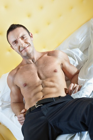 a very muscular man on a bed in a hotel room