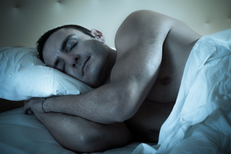 an handsome and muscular man sleeping peacefully on a bed