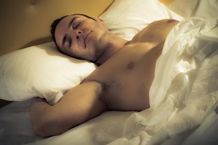 desnudo masculino: un hombre guapo y musculoso durmiendo plácidamente en una cama Foto de archivo