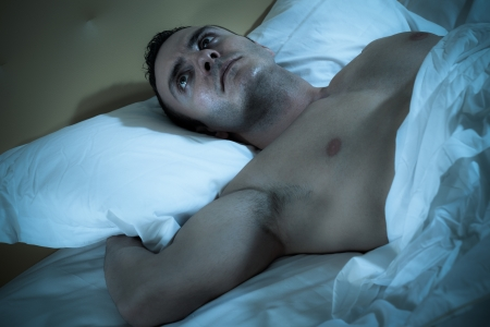 an handsome and muscular man thinking on a bed Stock Photo